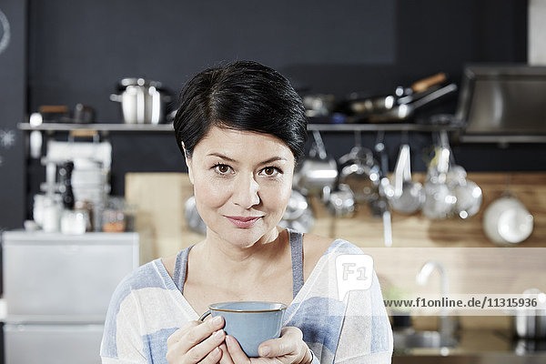 Portrait of woman in kitchen with cup of coffee