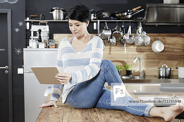 Woman sitting on table in kitchen looking on tablet