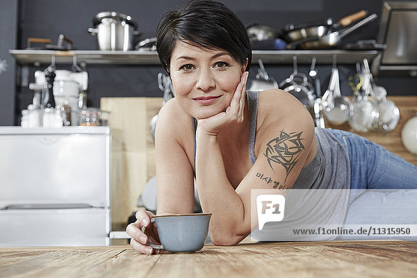 Portrait of smiling woman in kitchen with cup of coffee