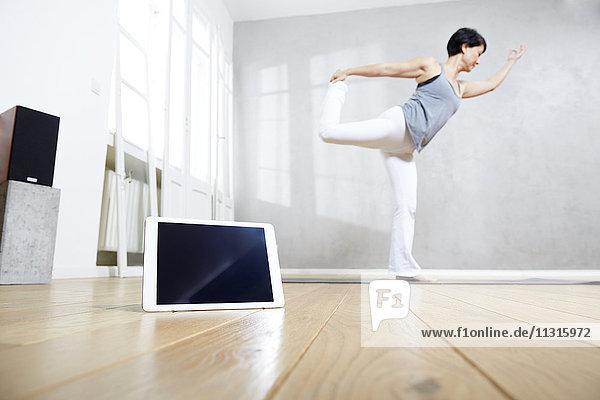 Woman practising yoga behind tablet