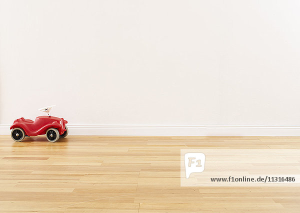 Red pedal car standing on parquet