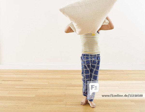 Kleiner Junge versteckt Gesicht hinter einem Kissen