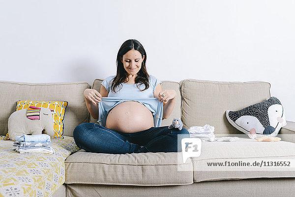 Schwangere Frau sitzt auf der Couch und zeigt den Bauch. Schwangere Frau sitzt auf der Couch und zeigt den Bauch.