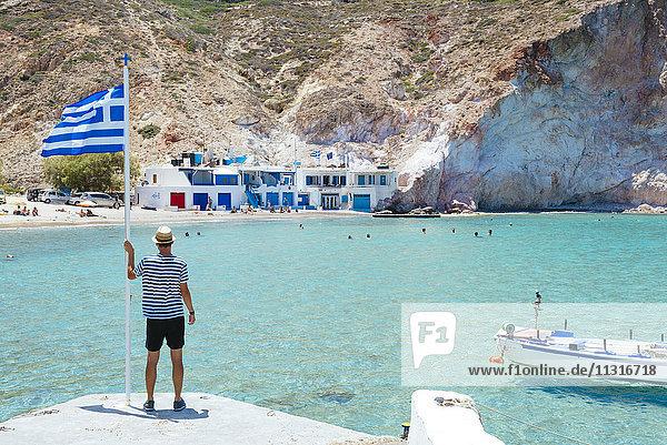 Griechenland  Milos  Firopotamos Beach  Mann schaut aufs Meer  hält die griechische Flagge fest