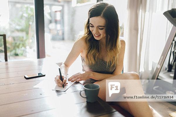 Lächelnde junge Frau schreibt zu Hause