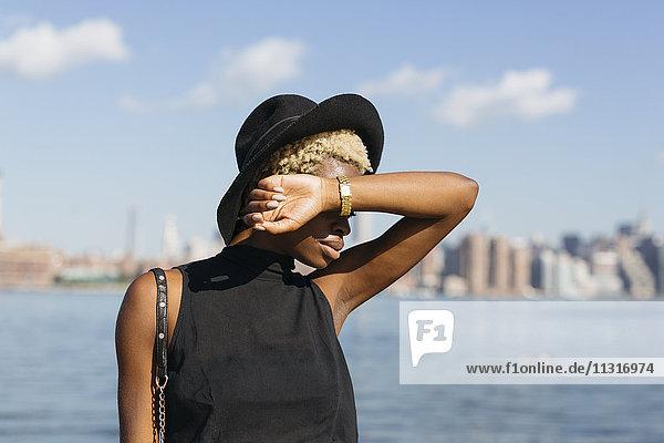 USA  New York City  Brooklyn  junge Frau mit Hut am East River