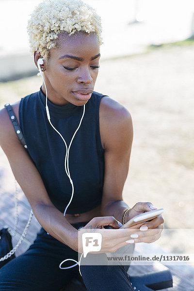 Junge Frau mit Handy und Ohrhörern