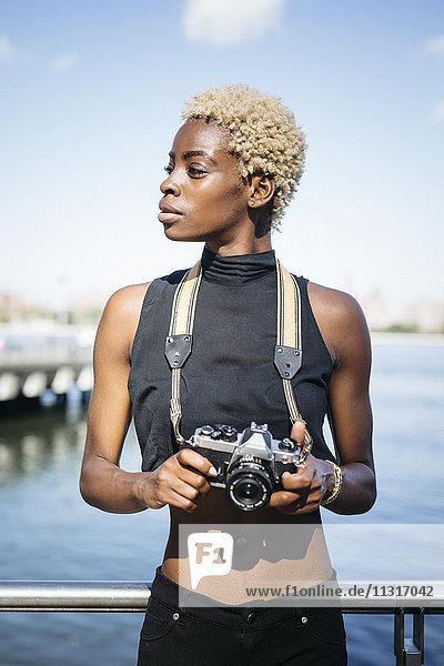 Junge Frau mit Kamera am Wasser schaut sich um