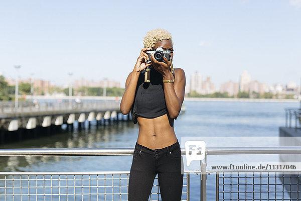 Junge Frau am Wasser beim Fotografieren