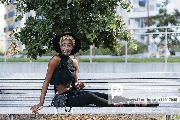 Junge Frau auf der Bank sitzend