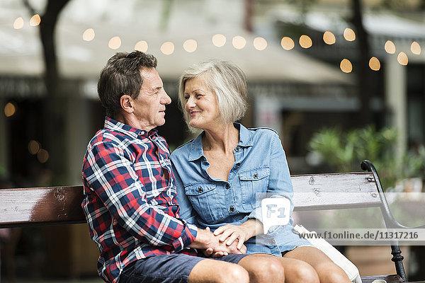 Seniorenpaar sitzt zusammen auf einer Bank und hält sich an den Händen.