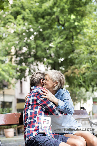 Fröhliches Seniorenpaar  das sich auf einer Bank umarmt.