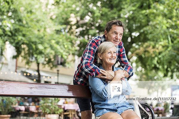 Älterer Mann  der seine Frau auf einer Bank umarmt.