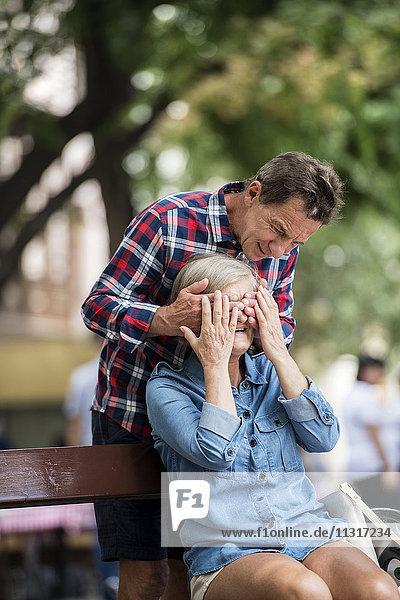 Älterer Mann  der die Augen seiner Frau bedeckt.