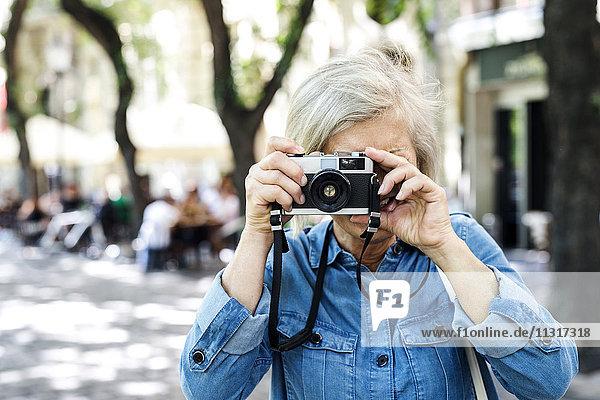 Seniorin beim Fotografieren mit der Kamera