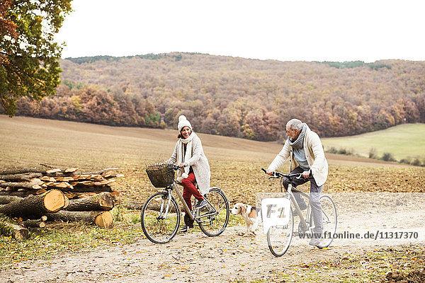 Seniorenpaar bei einer Fahrradtour mit Hund im Herbst