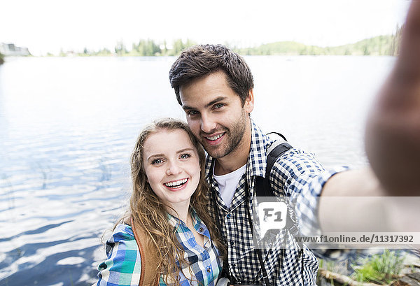 Young couple on a hiking tour at a lake taking a selfie