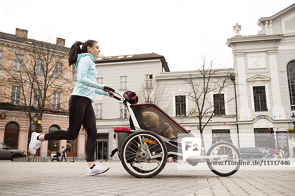 Mutter läuft mit Kind im Kinderwagen in der Stadt