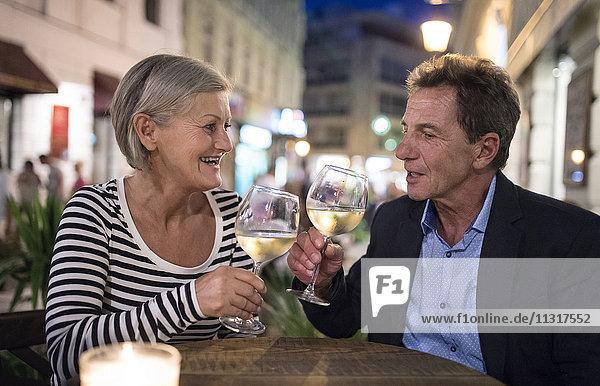 Seniorenpaar trinkt Wein an einer Bar im Freien