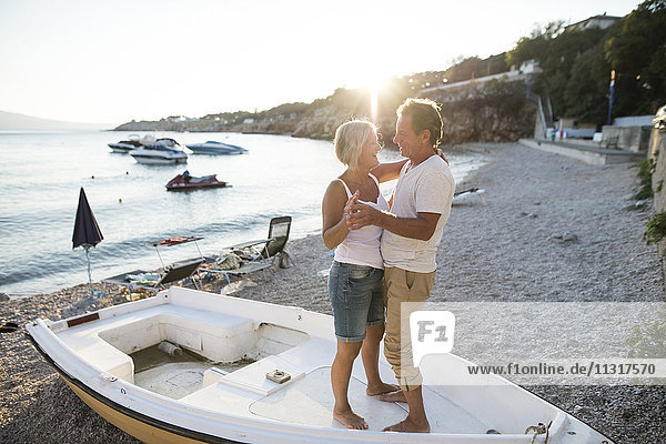 Senior couple dancing together on a boat lying on the beach at evening twilight