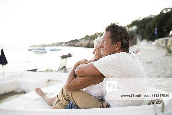 Seniorenpaar entspannt sich abends in einem Boot am Strand