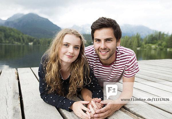 Verliebtes junges Paar liegt am Steg am See