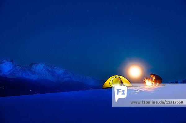 Seniorencamping in verschneiter Landschaft bei Vollmond