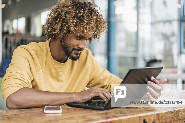 Junger Mann am Tisch sitzend  mit Laptop arbeitend