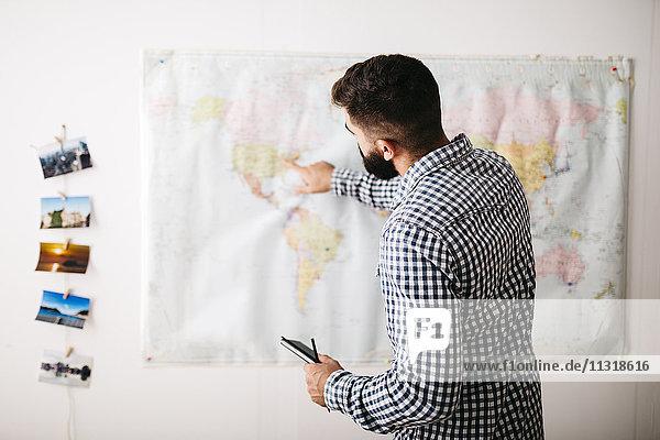 Junger Mann wählt Reiseziele auf einer Weltkarte aus