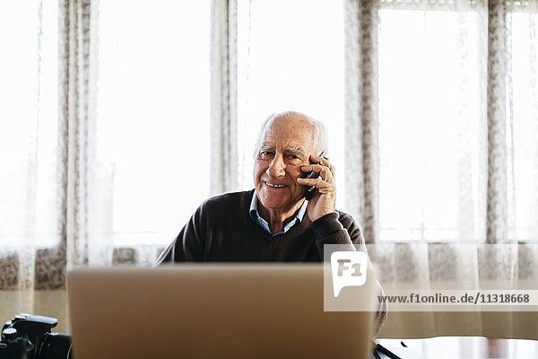 Porträt eines lächelnden älteren Mannes am Telefon zu Hause
