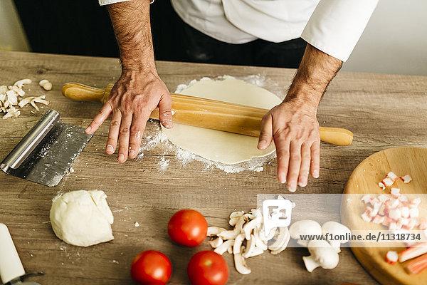 Koch bereitet Pizza zu