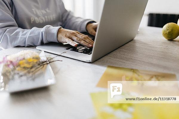 Frau mit Laptop  die von zu Hause aus arbeitet