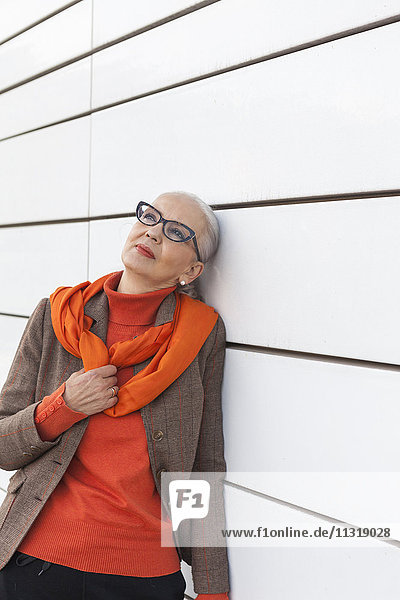 Portrait of fashionable mature woman leaning against white wall