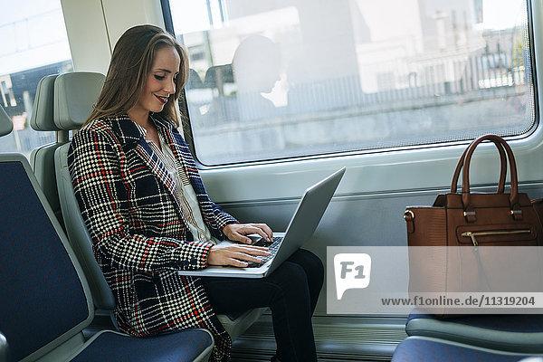 Geschäftsfrau im Zug mit Laptop