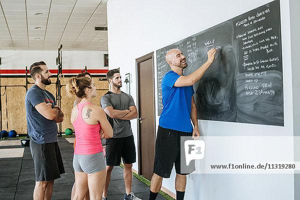 Trainer in einem Fitness-Kurs mit Tafelschreiben