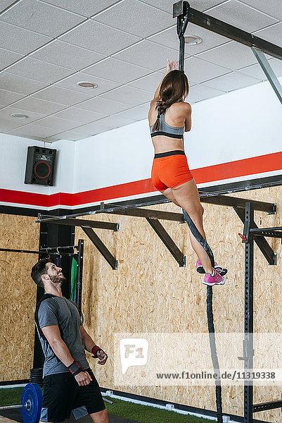 Mann beobachtet Frau beim Klettern in der Turnhalle