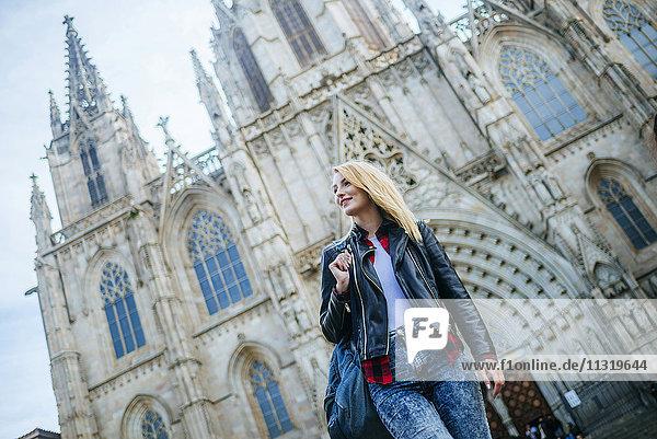 Spanien  Barcelona  lächelnde junge Frau  die vor der Kathedrale geht
