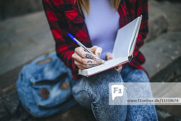 Tätowierte Frauenhandschrift im Notizbuch  Nahaufnahme