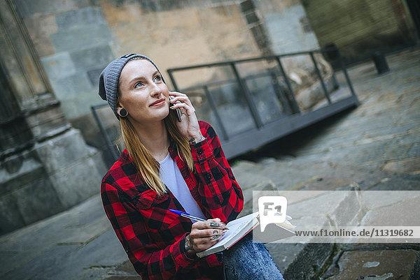 Spanien  Barcelona  Porträt einer lächelnden jungen Frau am Telefon auf einer Treppe sitzend mit Notizbuch