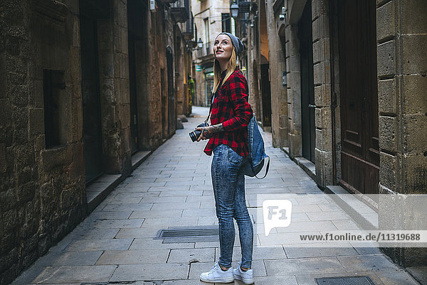 Spain  Barcelona  young woman taking pictures with reflex camera at Gothic Quarter