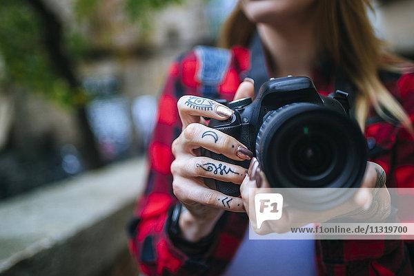 Tätowierte Frauenhände mit Spiegelreflexkamera  Nahaufnahme