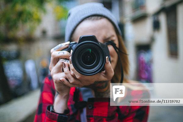 Junge Frau beim Fotografieren mit Spiegelreflexkamera Junge Frau beim Fotografieren mit Spiegelreflexkamera