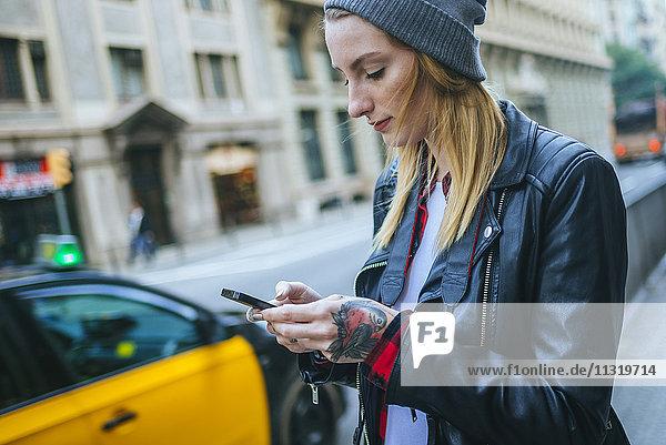 Spanien  Barcelona  junge Frau auf der Straße mit ihrem Handy