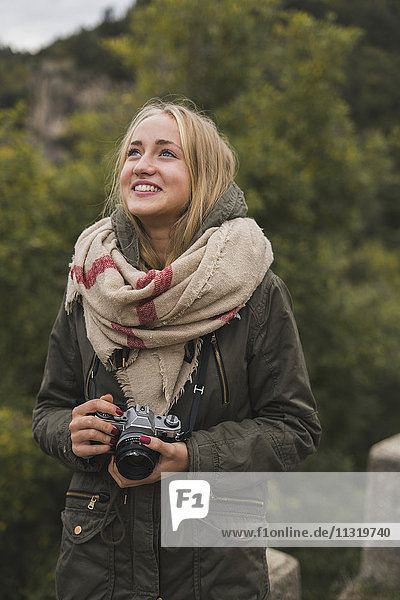 Lächelnde junge Frau mit Kamera im Freien