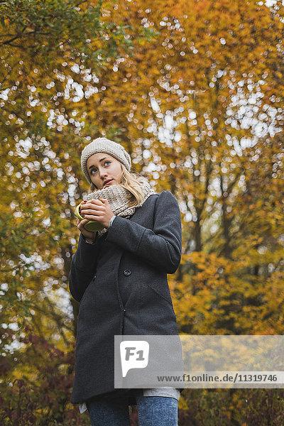 Junge Frau mit Heißgetränk im Herbstwald