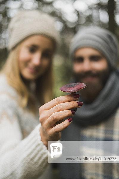 Junges Paar hält einen Pilz in der Hand