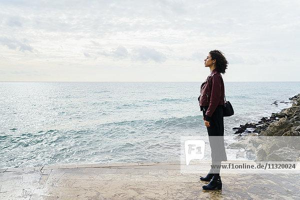 Frau steht vor dem Meer und schaut in die Ferne.