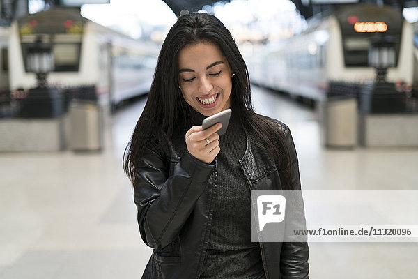 Glückliche junge Frau mit Handy am Bahnhof