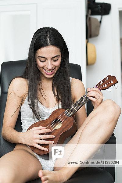 Junge Frau in Unterwäsche spielt Ukulele