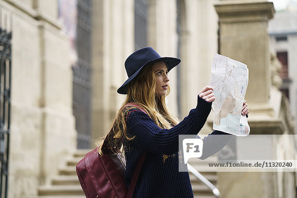 Tourist with backpack and city map watching something
